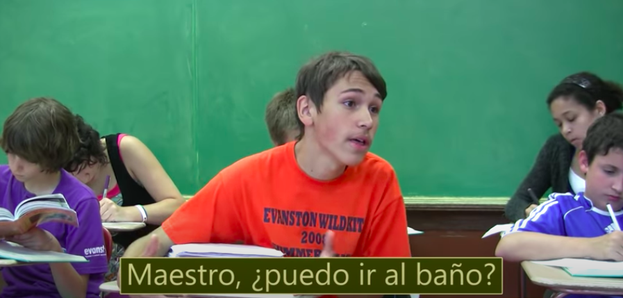 "A student in a classroom sings to his teacher ""Can I go to the bathroom"" in spanish."