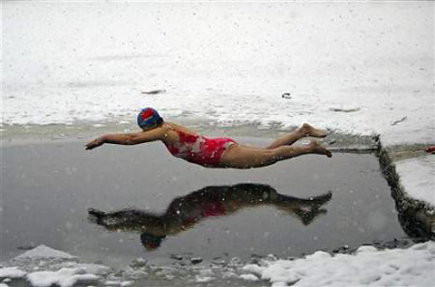 A winter swimmer jumps into icy water amid snowfall at a park in Shenyang, Liaoning province December 27, 2008. REUTERS/Stringer